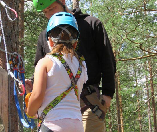 Instruktøren viser hva som er viktig å huske på i en klatrepark