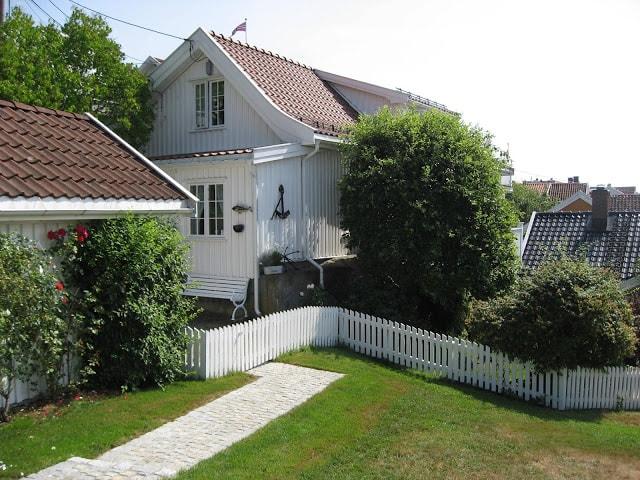 Et hvitmalt gammelt hus nes mot båthavna i Drøbak
