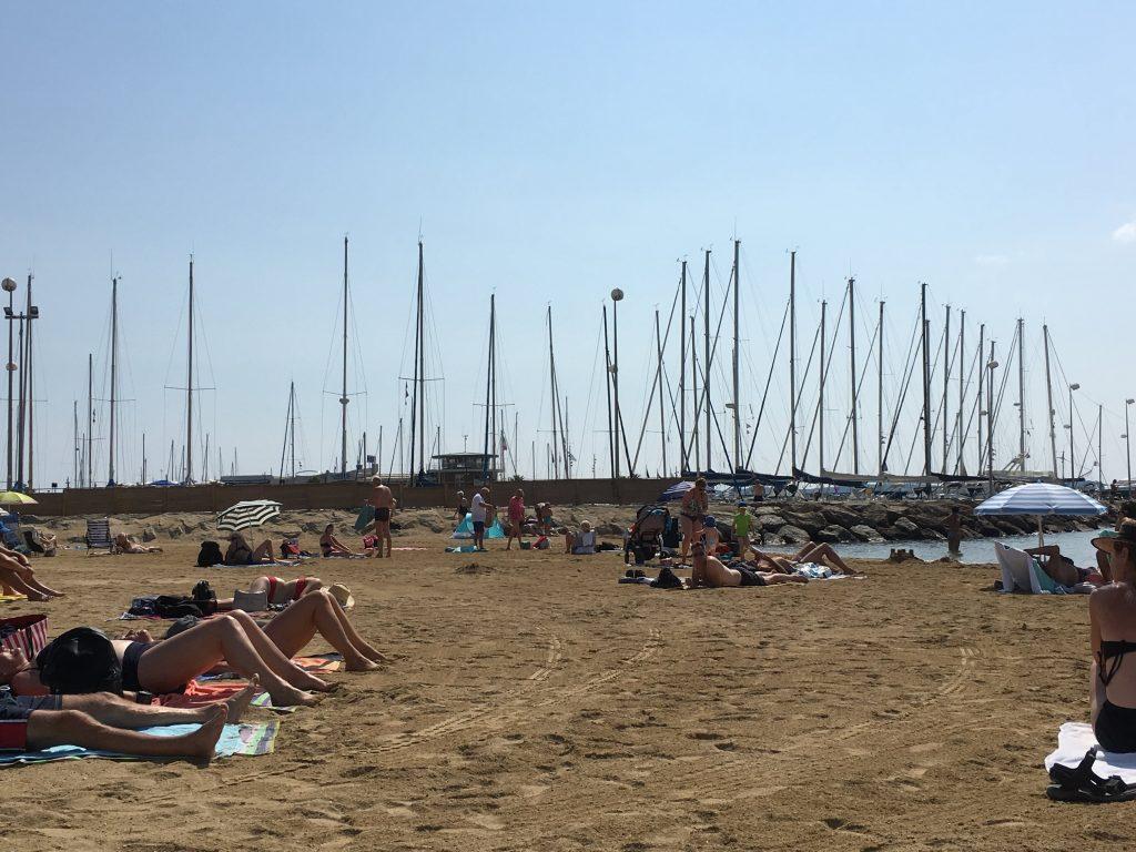Strand med båtmaster i bakgrunnen