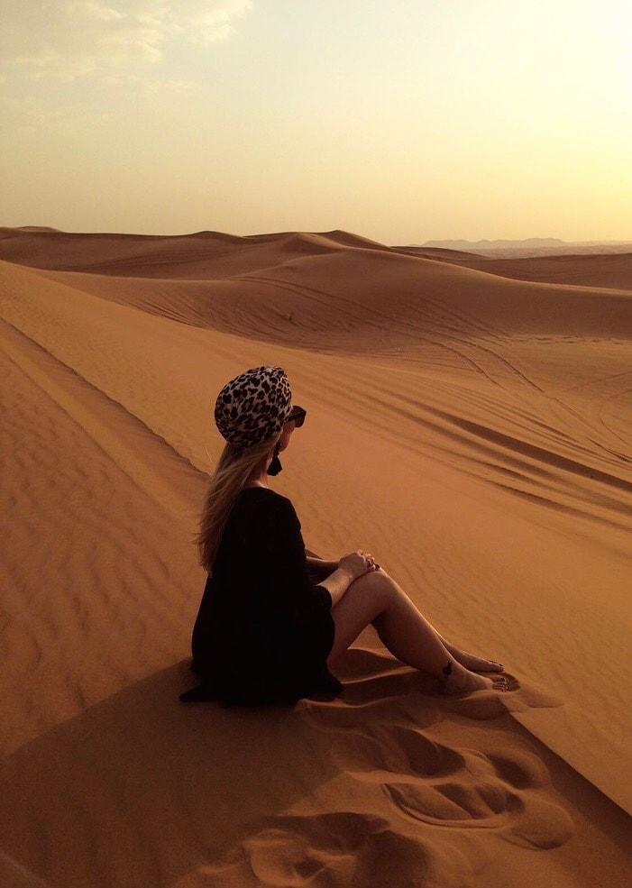 Christina sitter og ser utover ørkenen, Dubai