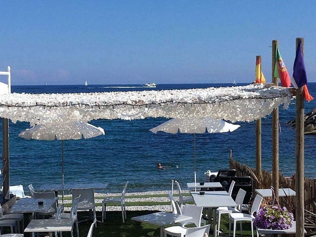 En alminnelig stranddag langs den franske riviera en strand- restaurant