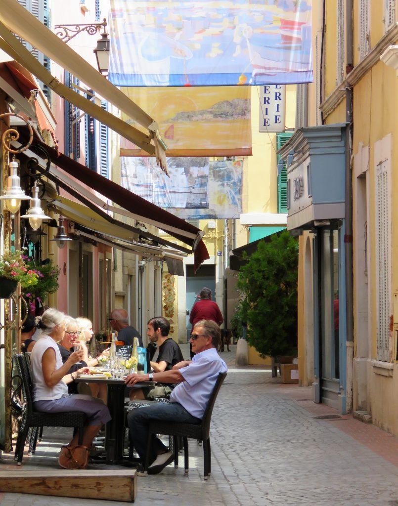Sanary-sur-mer i Provence, kystby. Folk koser seg ved en restaurant i byen. Urbantoglandlig.