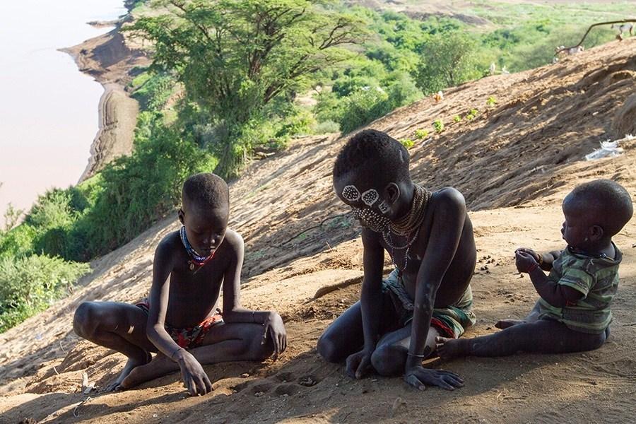Rystende og tankevekkende besøk hos stammefolk i Etiopia - Karo barn spiller mandala. De flytter steiner i groper i sanden.